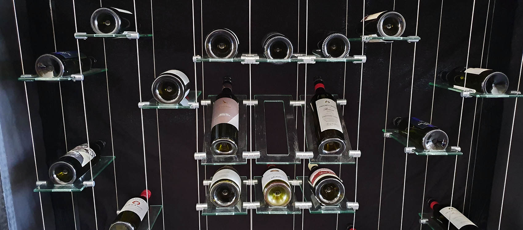 Floating glass wine rack system display with wine bottles filled